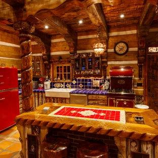 Kleine Rustikale Wohnküche in L-Form mit Landhausspüle, Schränken im Used-Look, Arbeitsplatte aus Fliesen, Küchenrückwand in Blau, Rückwand aus Keramikfliesen, bunten Elektrogeräten, Keramikboden, Kücheninsel und orangem Boden in Vancouver