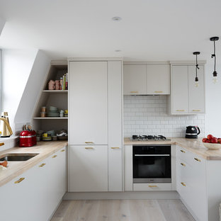 Mid-sized contemporary kitchen inspiration - Inspiration for a mid-sized contemporary u-shaped light wood floor and beige floor kitchen remodel in London with an undermount sink, flat-panel cabinets, beige cabinets, wood countertops, white backsplash, subway tile backsplash, black appliances and a peninsula