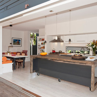 Design ideas for a medium sized contemporary l-shaped kitchen/diner in Sydney with a double-bowl sink, flat-panel cabinets, white cabinets, wood worktops, metallic splashback, glass sheet splashback, white appliances, light hardwood flooring and an island.