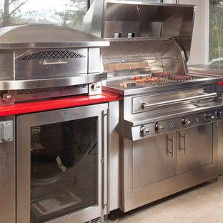 アトランタの大きいモダンスタイルのおしゃれなキッチン (クオーツストーンカウンター、シルバーの調理設備の、セラミックタイルの床、赤いキッチンカウンター) の写真