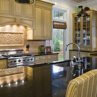 Свежая идея для дизайна: угловая кухня в классическом стиле с обеденным столом, накладной раковиной, фасадами с декоративным кантом, желтыми фасадами, гранитной столешницей, оранжевым фартуком, фартуком из терракотовой плитки, техникой из нержавеющей стали, паркетным полом среднего тона и островом - отличное фото интерьера