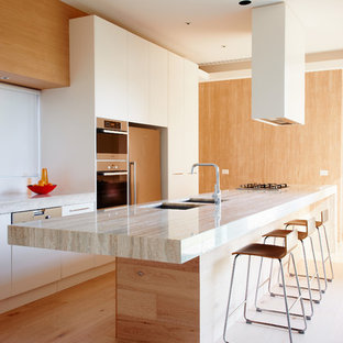 Kitchen - large modern galley light wood floor kitchen idea in Melbourne with a double-bowl sink, white cabinets, an island, flat-panel cabinets and paneled appliances