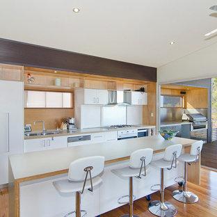 Foto de cocina lineal, marinera, con fregadero de doble seno, armarios con paneles lisos, puertas de armario blancas, suelo de madera clara y una isla