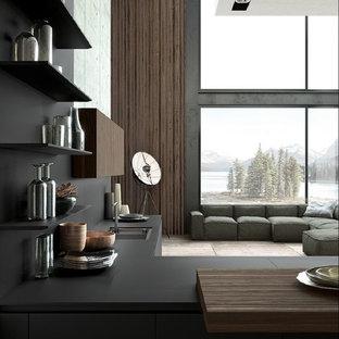 Пример оригинального дизайна: огромная угловая кухня-гостиная в современном стиле с накладной раковиной, плоскими фасадами, черными фасадами, столешницей из акрилового камня, черным фартуком, фартуком из каменной плиты, техникой под мебельный фасад, светлым паркетным полом, бежевым полом и черной столешницей без острова