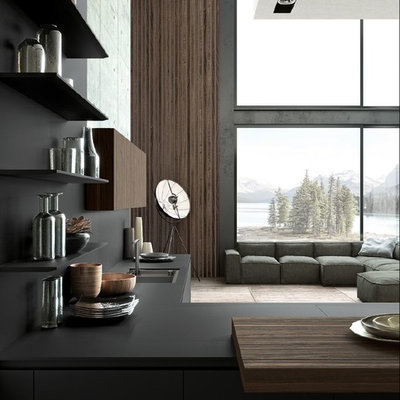 Inspiration for a huge contemporary l-shaped light wood floor and beige floor open concept kitchen remodel in San Francisco with a drop-in sink, flat-panel cabinets, black cabinets, solid surface countertops, black backsplash, stone slab backsplash, paneled appliances, no island and black countertops