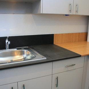 サンルイスオビスポの中サイズのエクレクティックスタイルのおしゃれなキッチン (ドロップインシンク、フラットパネル扉のキャビネット、グレーのキャビネット、木材カウンター、マルチカラーのキッチンパネル、カーペット敷き、アイランドなし、グレーの床、マルチカラーのキッチンカウンター) の写真