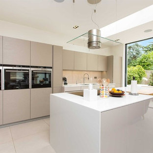 This is an example of a medium sized contemporary galley kitchen/diner in London with a double-bowl sink, flat-panel cabinets, beige cabinets, quartz worktops, glass sheet splashback, stainless steel appliances, an island, beige floors, white worktops and beige splashback.