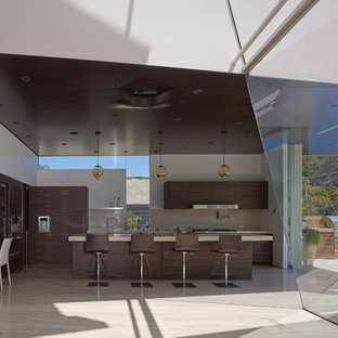 Design ideas for a mid-sized contemporary eat-in kitchen in Los Angeles with an integrated sink, flat-panel cabinets, dark wood cabinets, onyx benchtops, beige splashback, stone tile splashback, panelled appliances, travertine floors and with island.