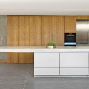 Design ideas for a large modern l-shaped open plan kitchen in Sydney with an integrated sink, flat-panel cabinets, medium wood cabinets, concrete benchtops, metallic splashback, metal splashback, black appliances, ceramic floors and with island.