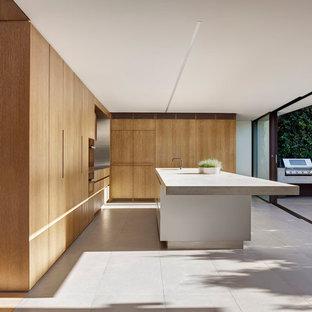 Ispirazione per una grande cucina moderna con lavello integrato, ante lisce, ante in legno scuro, top in cemento, paraspruzzi a effetto metallico, paraspruzzi con piastrelle di metallo, elettrodomestici neri, pavimento con piastrelle in ceramica e isola