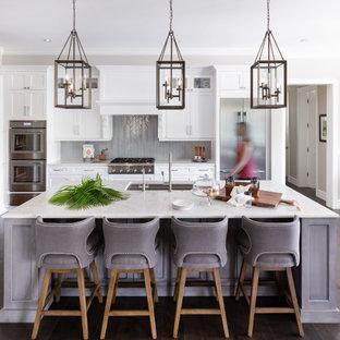 Inspiration för maritima vitt parallellkök, med en undermonterad diskho, skåp i shakerstil, vita skåp, grått stänkskydd, stänkskydd i mosaik, rostfria vitvaror, mörkt trägolv, en köksö och brunt golv