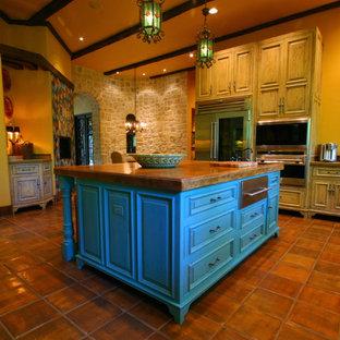 他の地域の巨大な地中海スタイルのおしゃれなキッチン (エプロンフロントシンク、レイズドパネル扉のキャビネット、淡色木目調キャビネット、木材カウンター、シルバーの調理設備の、テラコッタタイルの床) の写真