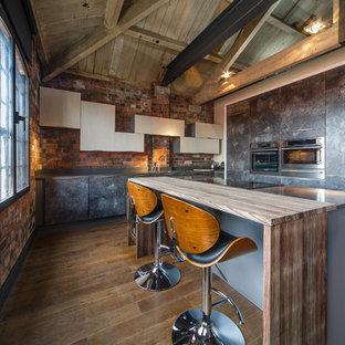 ウエストミッドランズの小さいインダストリアルスタイルのおしゃれなキッチン (フラットパネル扉のキャビネット、ヴィンテージ仕上げキャビネット、木材カウンター、レンガのキッチンパネル、シルバーの調理設備の、無垢フローリング、茶色い床) の写真