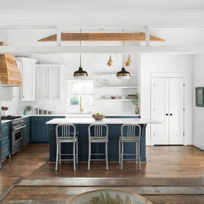 Inspiration for a country l-shaped medium tone wood floor and brown floor open concept kitchen remodel in New Orleans with a farmhouse sink, shaker cabinets, blue cabinets, white backsplash, subway tile backsplash, stainless steel appliances, an island, white countertops and marble countertops