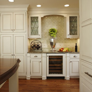 Inspiration for a large traditional l-shaped kitchen/diner in Detroit with a belfast sink, beaded cabinets, white cabinets, granite worktops, green splashback, metro tiled splashback, integrated appliances, medium hardwood flooring, an island, brown floors and brown worktops.