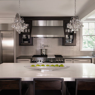 Photo of a mid-sized contemporary l-shaped eat-in kitchen in Birmingham with grey splashback, glass tile splashback, stainless steel appliances, dark hardwood floors, with island, quartz benchtops, flat-panel cabinets, dark wood cabinets, white benchtop, brown floor and a farmhouse sink.