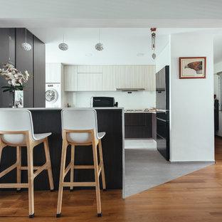 Inspiration för avskilda asiatiska vitt u-kök, med släta luckor, vita skåp, vitt stänkskydd, svarta vitvaror, en halv köksö och grått golv