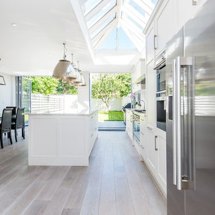 Design ideas for a classic galley kitchen/diner in London with white cabinets, shaker cabinets, stainless steel appliances, light hardwood flooring and an island.