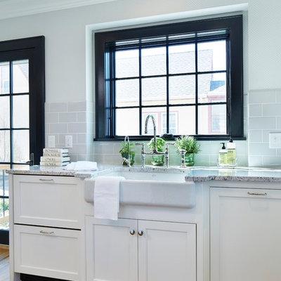 Transitional u-shaped medium tone wood floor kitchen photo in Minneapolis with a farmhouse sink, shaker cabinets, white cabinets, granite countertops, gray backsplash, subway tile backsplash, paneled appliances and an island
