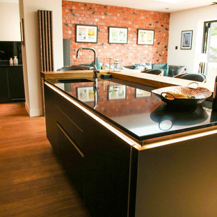 Inspiration for a large contemporary open plan kitchen in Other with an integrated sink, flat-panel cabinets, black cabinets, quartzite benchtops, black splashback, glass sheet splashback, black appliances, bamboo floors, with island and black benchtop.