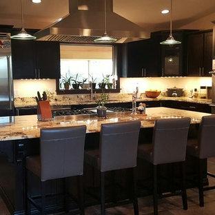 サンフランシスコの広いモダンスタイルのおしゃれなキッチン (ダブルシンク、フラットパネル扉のキャビネット、黒いキャビネット、御影石カウンター、ベージュキッチンパネル、石タイルのキッチンパネル、シルバーの調理設備、セラミックタイルの床、茶色い床、ベージュのキッチンカウンター) の写真