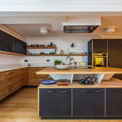 Inspiration for a mid-sized modern l-shaped light wood floor and beige floor kitchen remodel in Sussex with an undermount sink, flat-panel cabinets, medium tone wood cabinets, stainless steel appliances, an island, white countertops and wood countertops