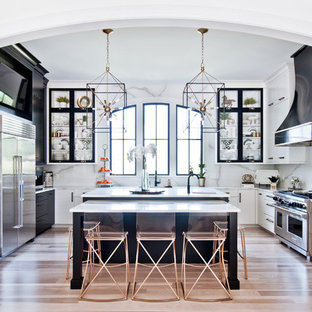 Cette photo montre une cuisine chic en U avec un placard à porte vitrée, des portes de placard noires, une crédence blanche, une crédence en dalle de pierre, un électroménager en acier inoxydable, un sol en bois clair, un îlot central, un sol beige et un plan de travail blanc.