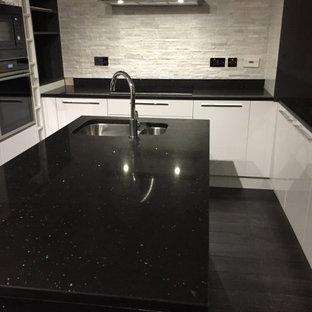 Idee per una cucina moderna di medie dimensioni con lavello a doppia vasca, ante di vetro, ante bianche, top in quarzite, paraspruzzi bianco, paraspruzzi in mattoni, elettrodomestici da incasso, pavimento in laminato, isola, pavimento nero e top nero
