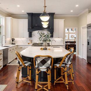 Стильный дизайн: п-образная кухня в классическом стиле с врезной раковиной, фасадами с выступающей филенкой, белыми фасадами, белым фартуком, техникой из нержавеющей стали, паркетным полом среднего тона, островом, красным полом и белой столешницей - последний тренд