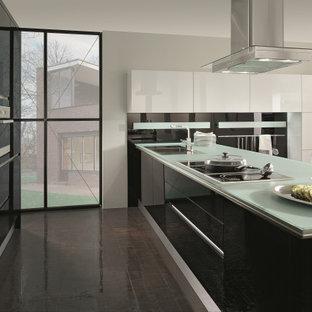 На фото: угловая кухня среднего размера в стиле модернизм с обеденным столом, накладной раковиной, плоскими фасадами, черными фасадами, стеклянной столешницей, черным фартуком, фартуком из стекла, техникой из нержавеющей стали, полом из керамогранита, полуостровом, коричневым полом и зеленой столешницей с