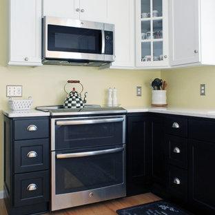 Kleine Klassische Wohnküche in U-Form mit Unterbauwaschbecken, Schrankfronten mit vertiefter Füllung, schwarzen Schränken, Quarzwerkstein-Arbeitsplatte, Küchenrückwand in Gelb, Küchengeräten aus Edelstahl, braunem Holzboden, Halbinsel und braunem Boden in Sonstige