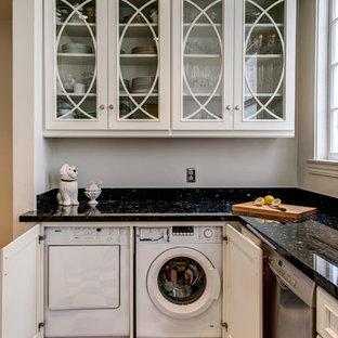 Inredning av ett klassiskt litet kök och matrum, med luckor med upphöjd panel, vita skåp, granitbänkskiva, svart stänkskydd, rostfria vitvaror och marmorgolv