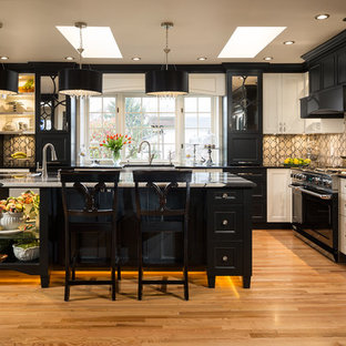 Traditional kitchen remodeling - Inspiration for a timeless l-shaped medium tone wood floor kitchen remodel in Vancouver with black appliances, raised-panel cabinets, black cabinets and an island