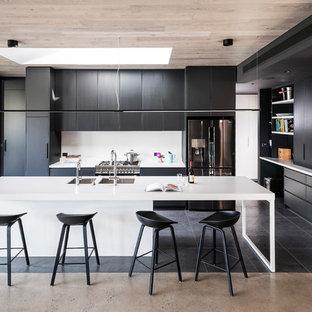 メルボルンの大きいモダンスタイルのおしゃれなアイランドキッチン (フラットパネル扉のキャビネット、黒いキャビネット、クオーツストーンカウンター、白いキッチンパネル、ガラス板のキッチンパネル、シルバーの調理設備の、磁器タイルの床、白いキッチンカウンター、ダブルシンク、黒い床) の写真