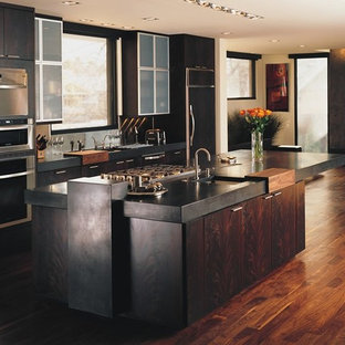 Mid-sized modern eat-in kitchen designs - Inspiration for a mid-sized modern single-wall medium tone wood floor eat-in kitchen remodel in Denver with flat-panel cabinets, dark wood cabinets, wood countertops, stainless steel appliances, an island, a drop-in sink and metallic backsplash
