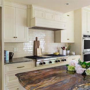 ミネアポリスの大きいトラディショナルスタイルのおしゃれなアイランドキッチン (エプロンフロントシンク、落し込みパネル扉のキャビネット、白いキャビネット、珪岩カウンター、白いキッチンパネル、サブウェイタイルのキッチンパネル、パネルと同色の調理設備、淡色無垢フローリング、茶色い床、マルチカラーのキッチンカウンター) の写真