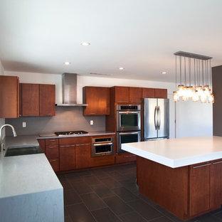 Esempio di una cucina a L american style con lavello stile country, ante lisce, ante in legno bruno, top in superficie solida, paraspruzzi grigio e elettrodomestici in acciaio inossidabile