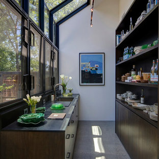 Country concrete floor kitchen photo in San Francisco with an undermount sink, dark wood cabinets and paneled appliances
