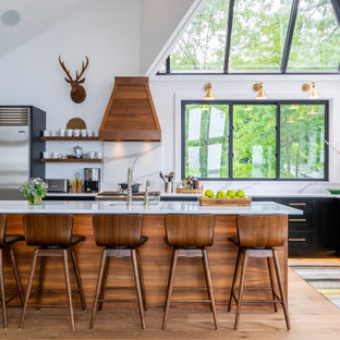Inspiration for a transitional l-shaped kitchen in Other with an undermount sink, shaker cabinets, black cabinets, white splashback, stone slab splashback, stainless steel appliances, medium hardwood floors, with island, brown floor, white benchtop and vaulted.