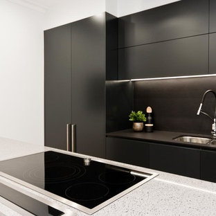 This is an example of a mid-sized modern single-wall eat-in kitchen in Sydney with a double-bowl sink, flat-panel cabinets, black cabinets, concrete benchtops, black splashback, with island, stone slab splashback, panelled appliances, laminate floors, grey benchtop and brown floor.