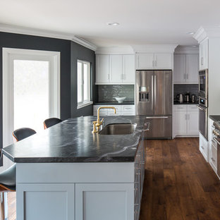 Large traditional u-shaped kitchen/diner in Los Angeles with a submerged sink, shaker cabinets, grey cabinets, marble worktops, grey splashback, porcelain splashback, stainless steel appliances, medium hardwood flooring and an island.