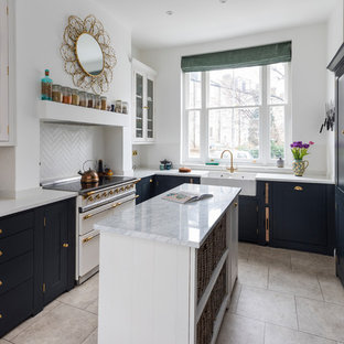 Photo of a small traditional l-shaped kitchen/diner in London with a belfast sink, shaker cabinets, black cabinets, quartz worktops, limestone flooring, an island, beige floors, white splashback and white appliances.