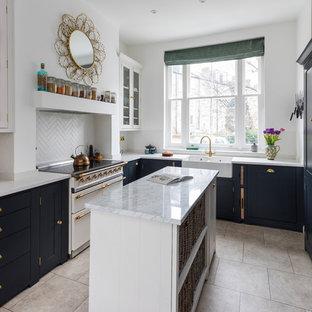 Klassisk inredning av ett litet kök, med en rustik diskho, skåp i shakerstil, svarta skåp, bänkskiva i kvartsit, kalkstensgolv, en köksö, beiget golv, vitt stänkskydd och vita vitvaror