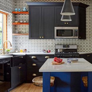 Inspiration för lantliga vitt l-kök, med en rustik diskho, skåp i shakerstil, svarta skåp, vitt stänkskydd, stänkskydd i cementkakel, svarta vitvaror, mellanmörkt trägolv, en köksö och brunt golv