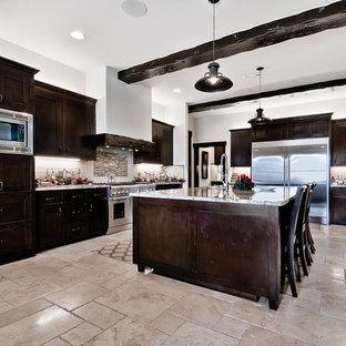 他の地域の大きいラスティックスタイルのおしゃれなキッチン (アンダーカウンターシンク、シェーカースタイル扉のキャビネット、濃色木目調キャビネット、御影石カウンター、白いキッチンパネル、サブウェイタイルのキッチンパネル、シルバーの調理設備の、トラバーチンの床、ベージュの床) の写真