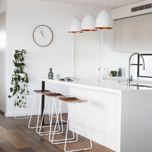 This is an example of a contemporary kitchen in Melbourne with a double-bowl sink, flat-panel cabinets, white cabinets, window splashback, dark hardwood floors and with island.