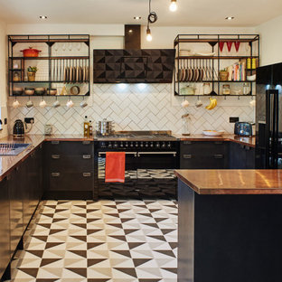 Photo of a mid-sized modern u-shaped eat-in kitchen in Sussex with a drop-in sink, flat-panel cabinets, black cabinets, copper benchtops, white splashback, subway tile splashback, black appliances, ceramic floors, a peninsula and multi-coloured floor.