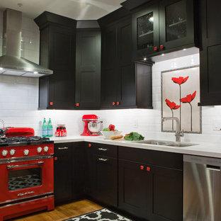 На фото: большая угловая кухня в стиле фьюжн с обеденным столом, плоскими фасадами, черными фасадами, столешницей из кварцевого композита, белым фартуком, фартуком из керамической плитки, цветной техникой, двойной раковиной и паркетным полом среднего тона без острова с