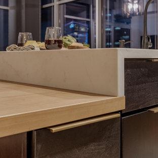 小さいモダンスタイルのおしゃれなキッチン (アンダーカウンターシンク、フラットパネル扉のキャビネット、黒いキャビネット、クオーツストーンカウンター、白いキッチンパネル、シルバーの調理設備の、茶色い床、白いキッチンカウンター) の写真