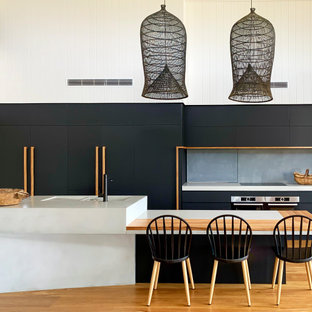 Photo of a contemporary open plan kitchen in Sunshine Coast with flat-panel cabinets, black cabinets, concrete benchtops, grey splashback, with island, grey benchtop, an integrated sink, panelled appliances, medium hardwood floors and brown floor.